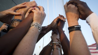 People of different races hold hands as they gather on the Arthur Ravenel Jr. bridge in Charleston